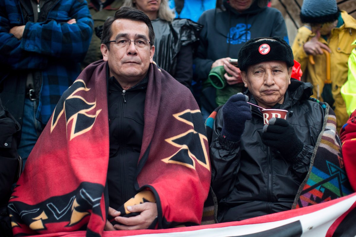 Union of B.C. Indian Chiefs Vice President Chief Bob Chamberlin, left, and Grand Chief Stewart Phillip, President of the Union of B.C. Indian Chiefs, join protesters opposed to the Kinder Morgan Trans Mountain pipeline extension and defy a court order blocking an entrance to the company's property, in Burnaby, B.C., on Saturday April 7, 2018.