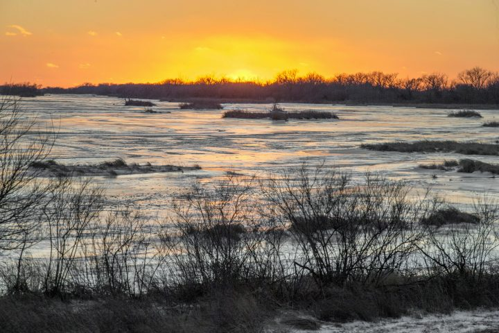 In this Feb. 7, 2019 photo, the sun sets behind the ice-covered Platte River in Columbus, Neb. Mentioning climate change can kill a conversation. But a new Alberta project is using the topic to start one - and has shown people from geologists to farmers to environmentalists they have more in common than they thought.