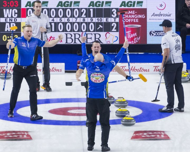 Team Wild Card skip Brendan Bottcher (back left) looks on as Team Alberta skip Kevin Koe, third B.J. Neufeld, second Colton Flasch and lead Ben Hebert celebrate their win following the final rock at the Brier in Brandon, Man. Sunday, March 10, 2019.