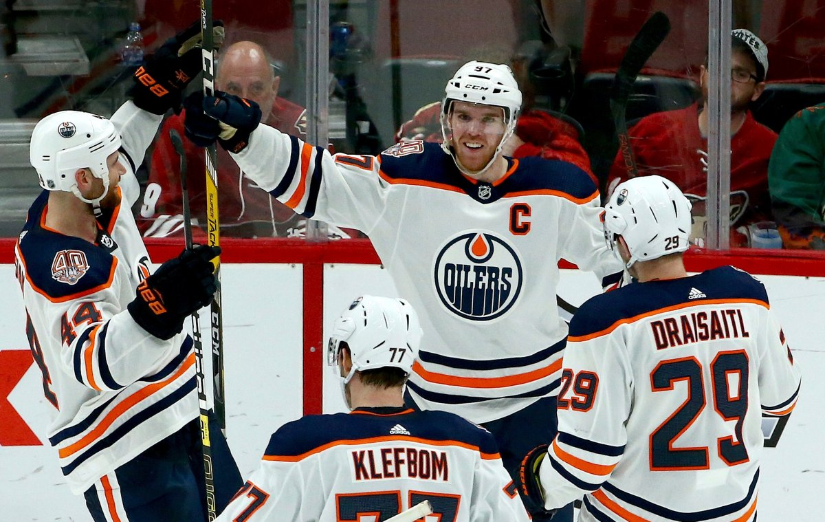 Edmonton Oilers center Connor McDavid (97) smiles as he celebrates his game-winning goal against the Arizona Coyotes with Zack Kassian (44), Oscar Klefbom (77) and Leon Draisaitl (29) during overtime of an NHL hockey game Saturday, March 16, 2019, in Glendale, Ariz. The Oilers won 3-2.