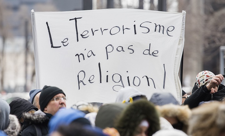 People hold up signs as they attend a vigil in Montreal, Sunday, March 17, 2019, following a shooting at a mosque in Christchurch, New Zealand which left 50 people dead and many more injured.