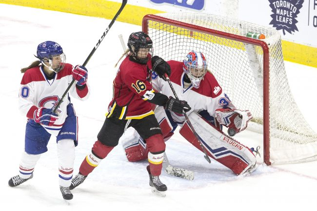 Calgary Inferno's Rebecca Leslie (centre) tries to tip the puck past Les Canadiennes de Montreal's goaltender Emerance Maschmeyer during second period action in the 2019 Clarkson Cup game in Toronto, March 24, 2019.