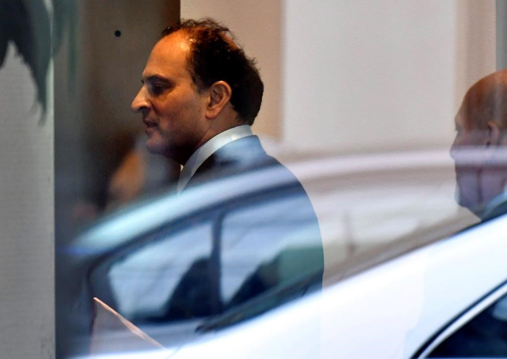 David Sidoo, of Vancouver enters an adjacent building with his lawyer following a federal court hearing Friday, March 15, 2019, in Boston. Sidoo faced charges of conspiracy to commit mail and wire fraud as part of a wide-ranging college admissions bribery scandal.