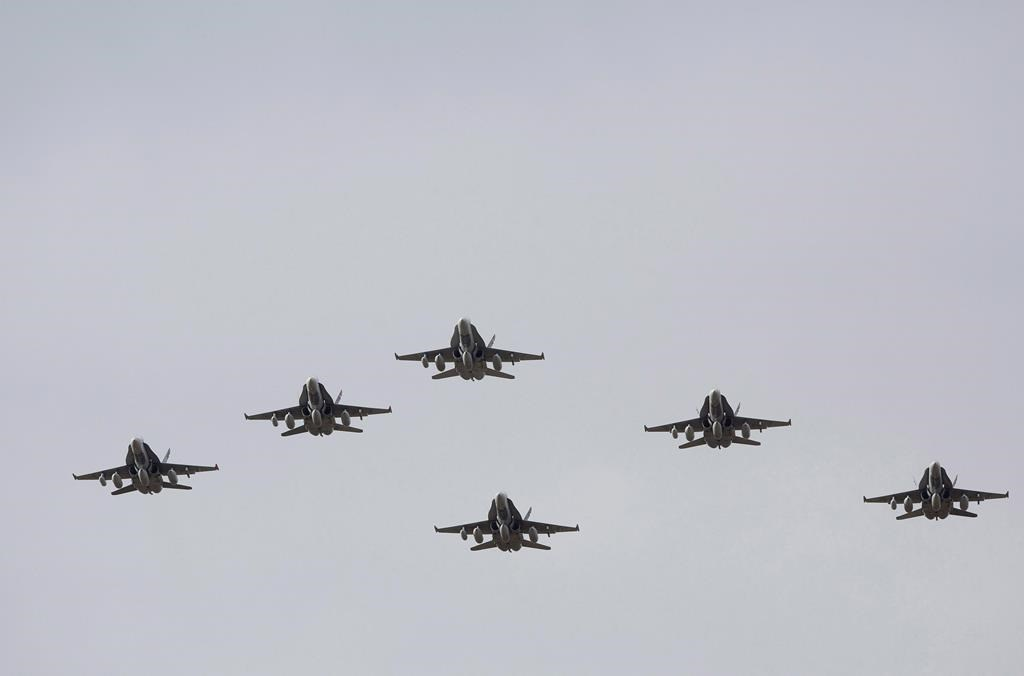 CF-18 Hornets fly in formation on their the departure for Operation IMPACT, in Cold Lake, Alberta on Tuesday October 21, 2014. THE CANADIAN PRESS/Jason Franson.