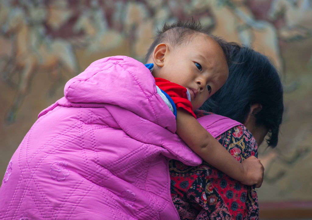 In this Sept. 11, 2008 file photo, a North Korean woman carries a boy on her back in Sariwon, North Korea.