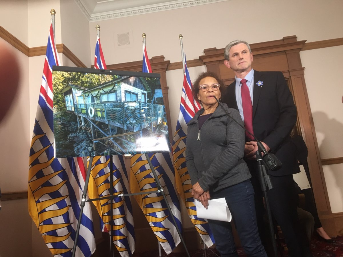 Belcarra property owner Charline Robson and Liberal leader Andrew Wilkinson standing beside a picture of Robson's summer cabin.