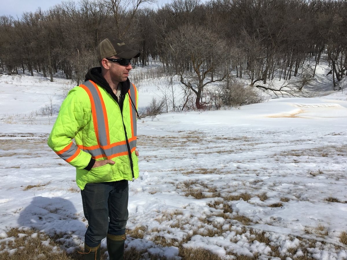 Jason Parker standing on the dyke that protects his family's home from flooding from the Red River.