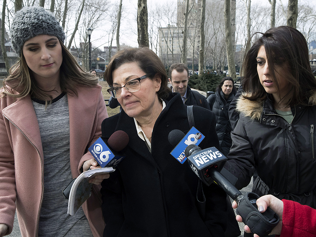 Nancy Salzman, centre, is surrounded by reporters as she arrives at Brooklyn federal court, Wednesday, March 13, 2019, in New York.