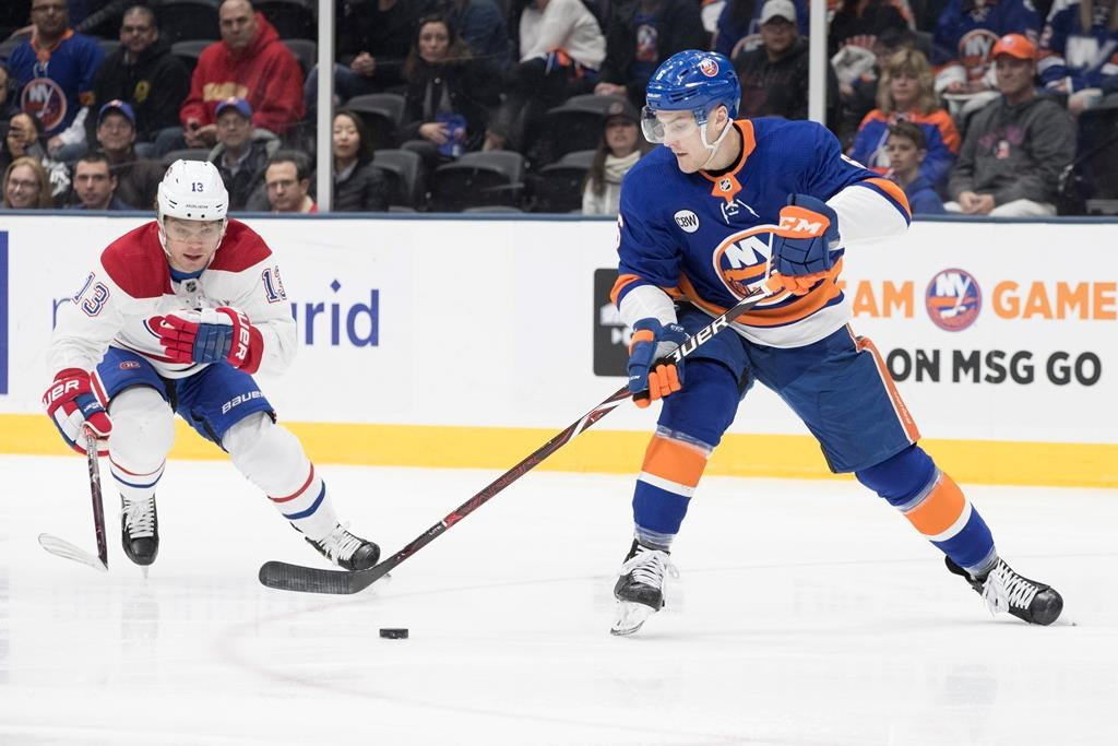 New York Islanders defenseman Ryan Pulock (6) skates against Montreal Canadiens center Max Domi (13) during the first period of an NHL hockey game, Thursday, March 14, 2019, in Uniondale, N.Y.