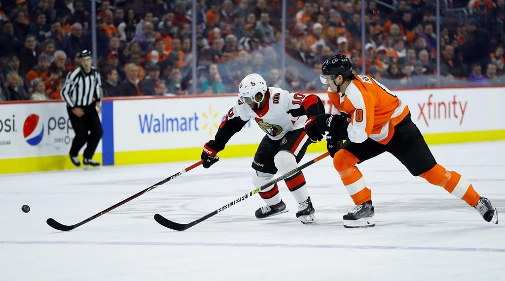 Ottawa Senators' Anthony Duclair, left, and Philadelphia Flyers' Robert Hagg chase after the puck during the first period of an NHL hockey game, Monday, March 11, 2019, in Philadelphia.