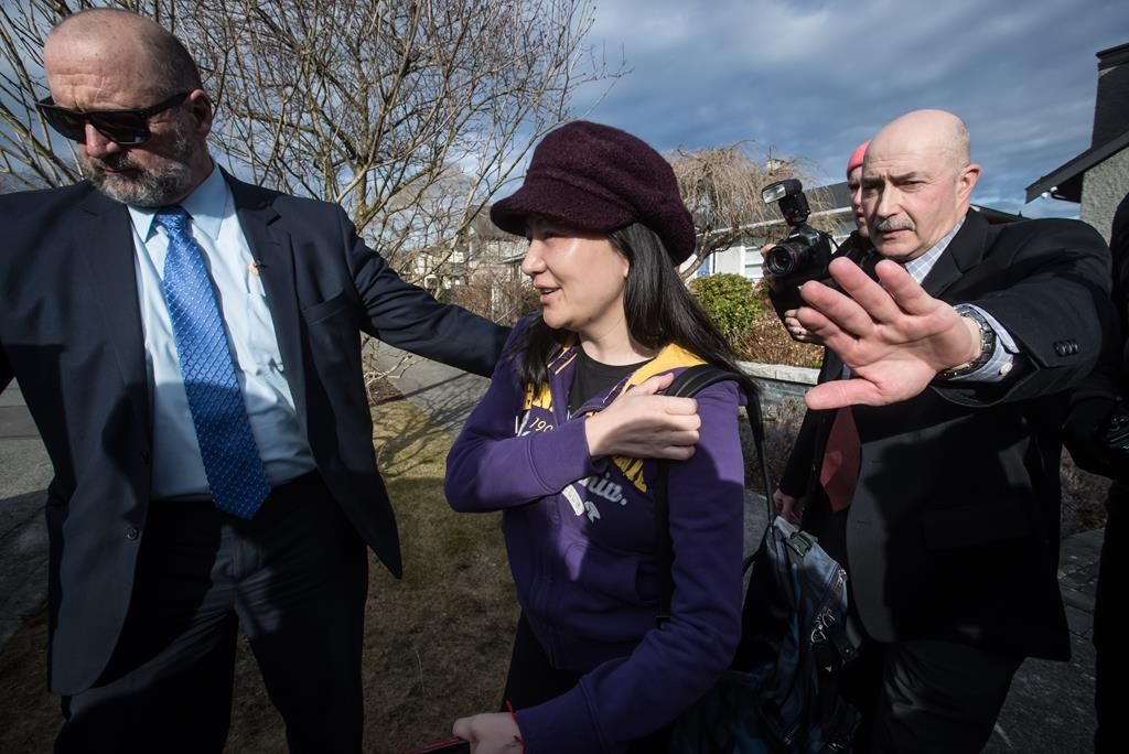 Huawei chief financial officer Meng Wanzhou, centre, who is out on bail and remains under partial house arrest after she was detained Dec. 1 at the behest of American authorities, is accompanied by a private security detail as she leaves her home to attend a court appearance in Vancouver, on Wednesday March 6, 2019.