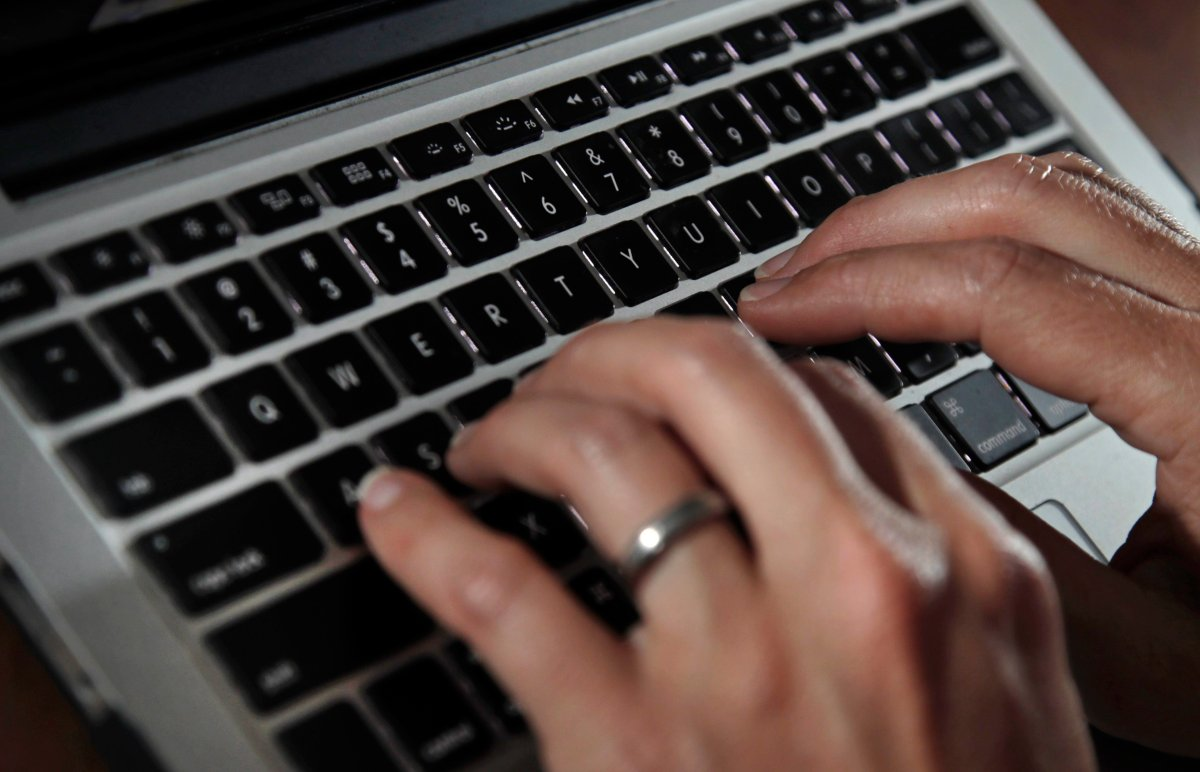 FILE- In this June 19, 2017, file photo, a person types on a laptop keyboard in North Andover, Mass. (AP Photo/Elise Amendola, File).