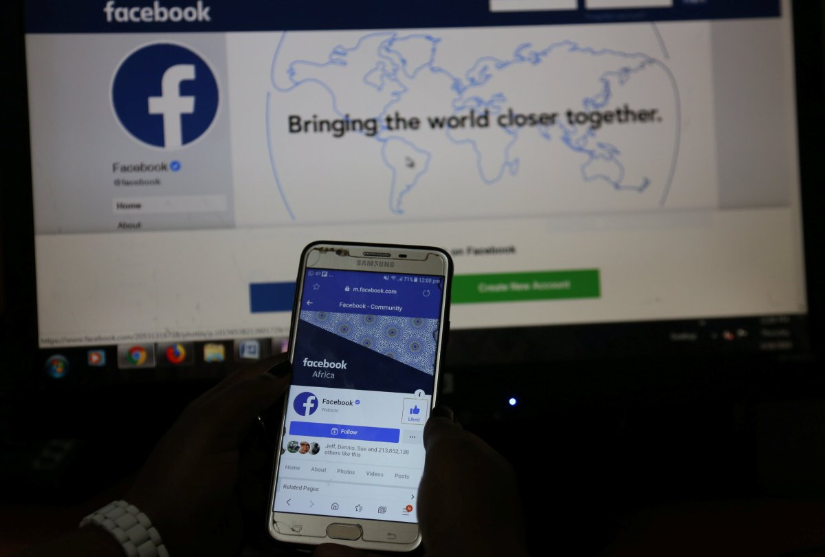 An illustration photo shows the Facebook page displayed on a mobile phone internet browser held in front of a computer screen.