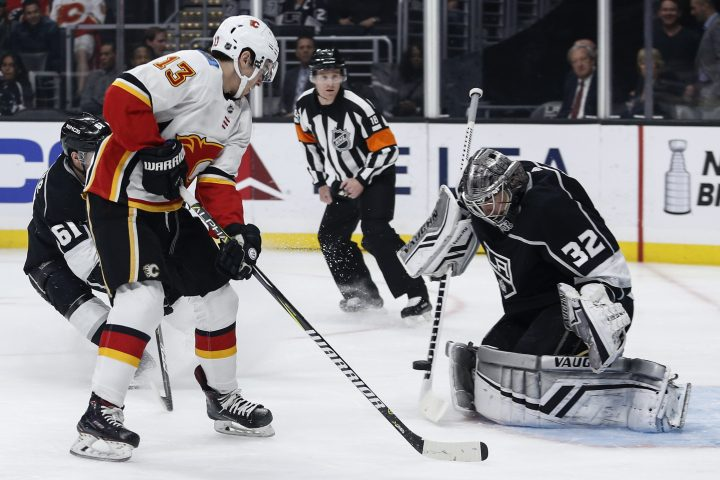 Los Angeles Kings goalie Jonathan Quick (32) blocks a shot by Calgary Flames forward Johnny Gaudreau (13) during the first period of an NHL hockey game Monday, April 1, 2019, in Los Angeles.