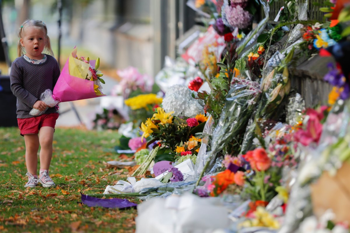 In this March 17, 2019, file photo, a girl carries flowers to a memorial wall following the mosque shootings in Christchurch, New Zealand.