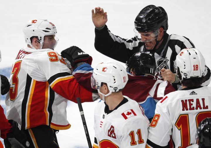 Linesman Bryan Pancich, back, tries to separate Calgary Flames center Sam Bennett, front left, and Colorado Avalanche left wing Matt Calvert as they fight in the third period of Game 3 of a first-round NHL hockey playoff series, Monday, April 15, 2019, in Denver. The Avalanche won 6-2.
