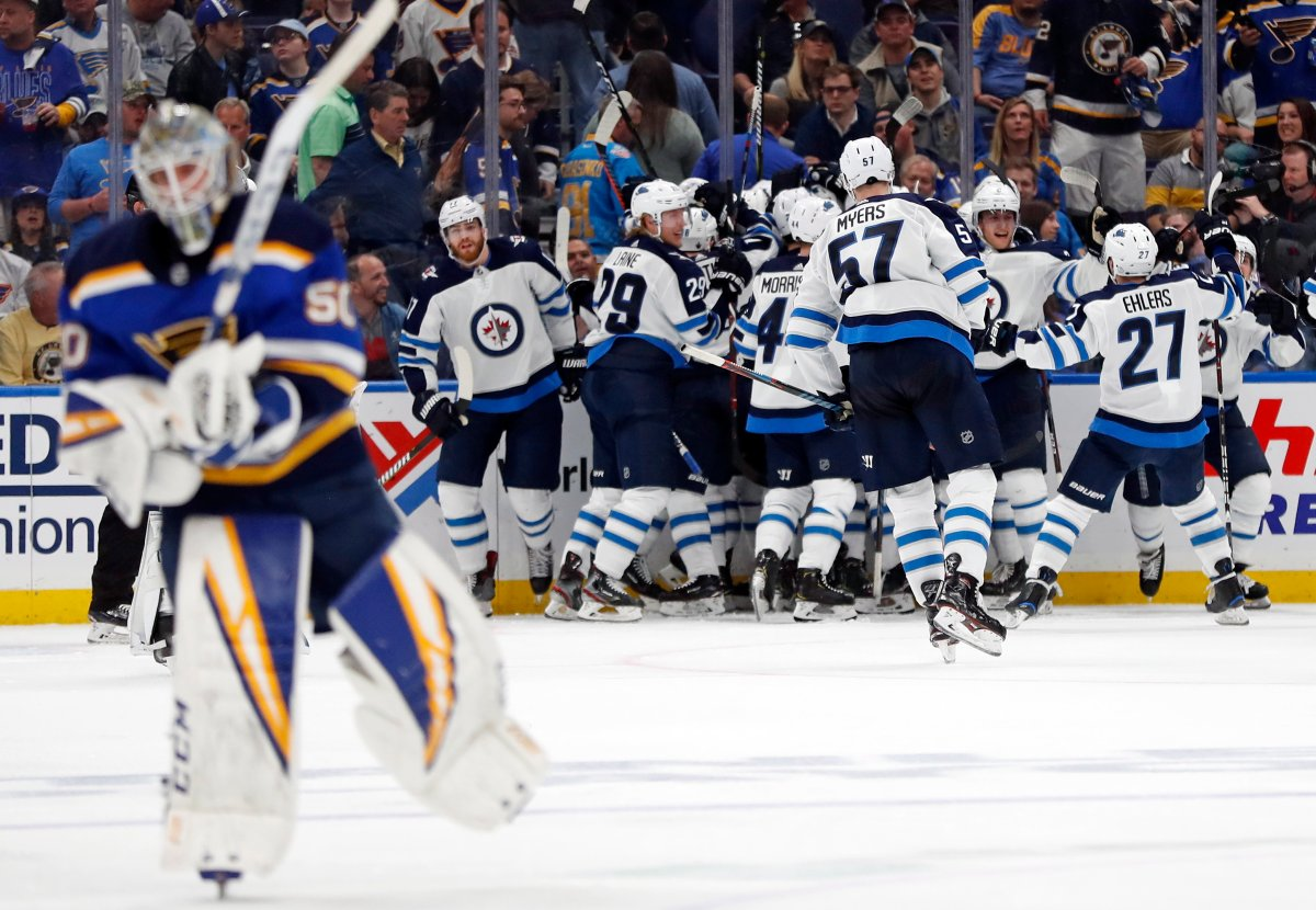 Winnipeg Jets celebrate as St. Louis Blues goaltender Jordan Binnington, left, skates to the bench after Jets left wing Kyle Connor scored during overtime in Game 4 of an NHL hockey first-round playoff series Tuesday, April 16, 2019, in St. Louis. The Jets won 2-1 to even the series 2-2. (AP Photo/Jeff Roberson).