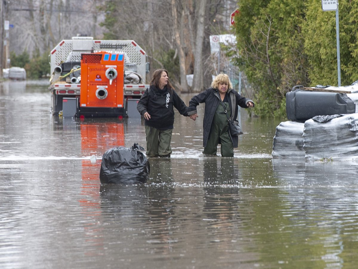 File - Residents wade through a flooded street Thursday, April 25, 2019 in Laval, Que.