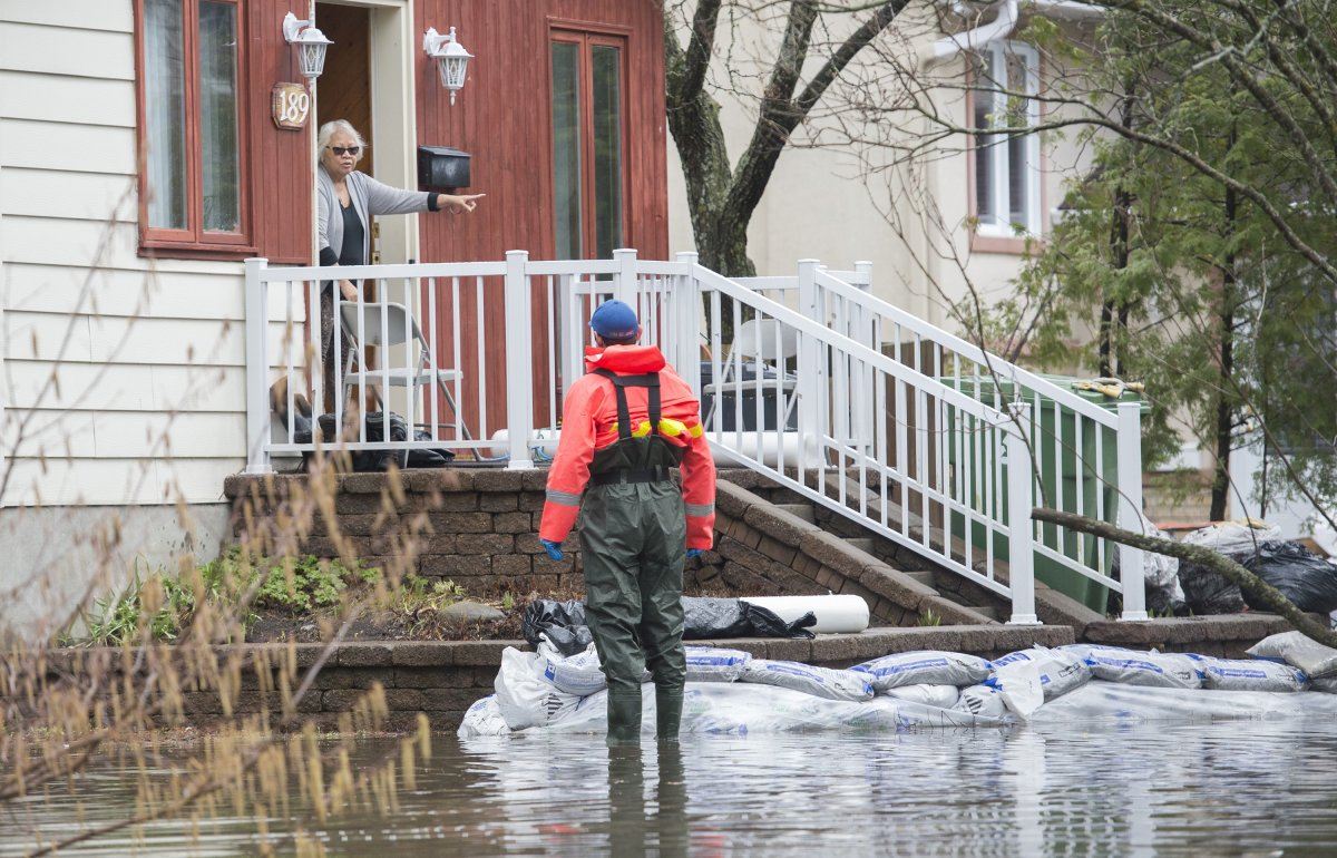 A woman talks to a volunteer emergency worker at her home on a residential street surrounded by floodwaters on Île-Bizard west of Montreal, Saturday, April 27, 2019.
