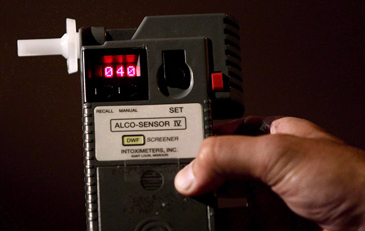 An officer holds a breathalyzer test showing a blood-alcohol reading of .04 in this file photo.