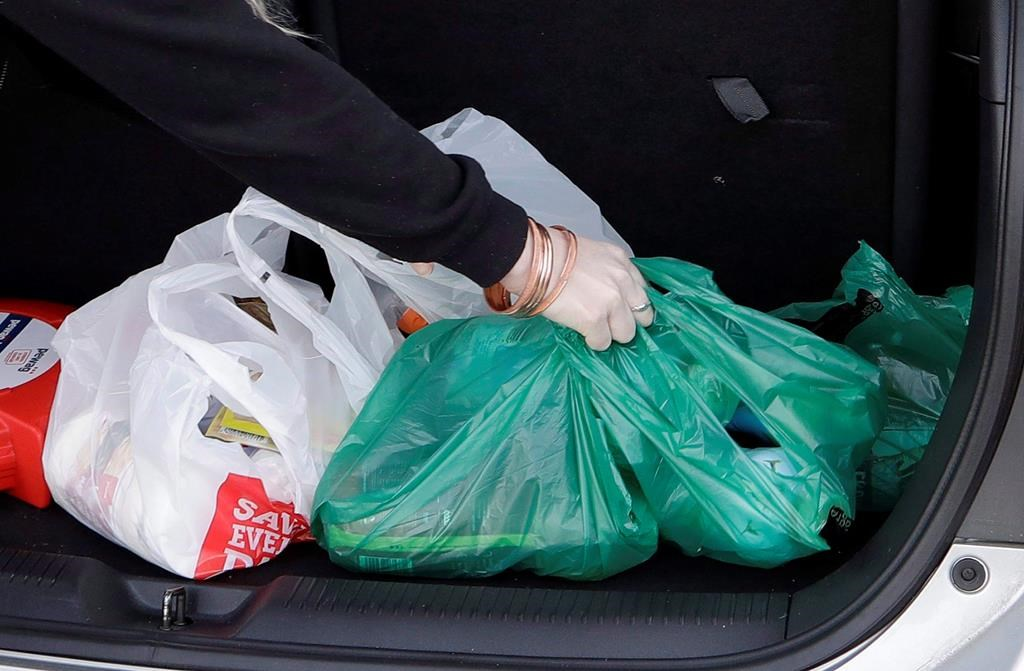 A shopper places her goods into her car outside a supermarket in Christchurch, New Zealand, Friday, Aug. 10, 2018. Newfoundland and Labrador has announced it will become the second province to ban plastic bags.