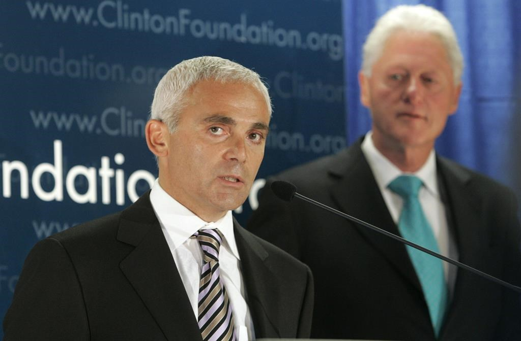 """Frank Giustra, a Canadian businessman, speaks as former President Bill Clinton looks on during a news conference to announce the Clinton Foundation's launching of a new sustainable development initiative in Latin America Thursday, June 21, 2007 in New York. A British Columbia businessman and philanthropist is suing Twitter for publishing """"false and defamatory"""" tweets that escalated during the 2016 United States election. Frank Giustra is the founder of Lionsgate Entertainment and CEO of the Fiore Group of Companies, and he's also a member of the board of trustees of the Clinton Foundation."""