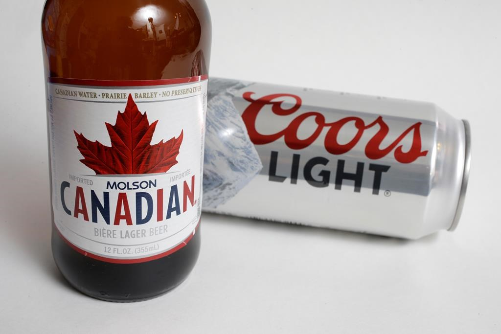 In this Feb. 14, 2018, file photo, Molson Coors products Molson Canadian beer, left, and Coors Light beer are shown in Walpole, Mass. THE CANADIAN PRESS/AP Photo/Steven Senne, File.