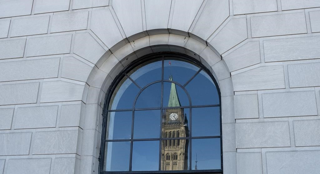 The Peace tower is reflected in a window in Ottawa, Tuesday March 26, 2019.
