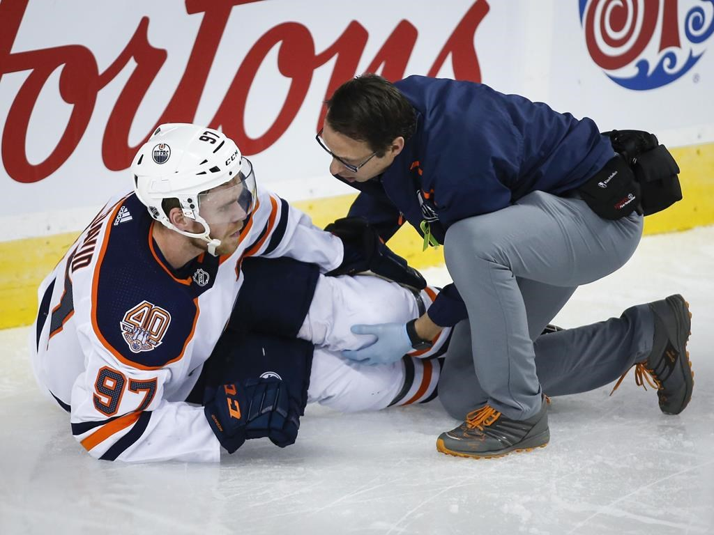 Edmonton Oilers' Connor McDavid, left, has his knee tended too after crashing into Calgary Flames goalie Mike Smith during second period NHL hockey action in Calgary, Saturday, April 6, 2019. McDavid will begin rehabilitating his leg immediately, the Edmonton Oilers announced late Friday. THE CANADIAN PRESS/Jeff McIntosh.