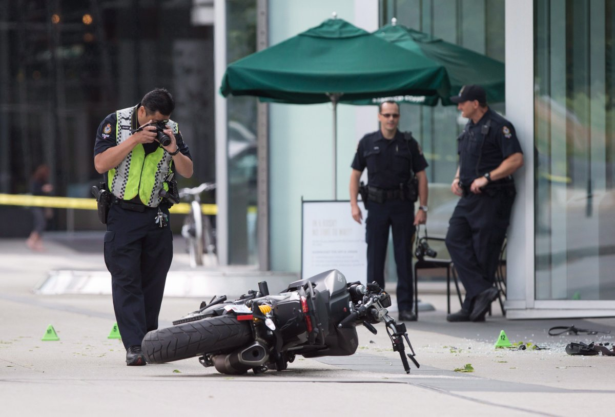 """A police officer photographs a motorcycle after a female stunt driver working on the movie """"Deadpool 2"""" died after a crash on set, in Vancouver, B.C., on Monday August 14, 2017. The studio behind the film has settled with the family of S.J. """"Joi"""" Harris."""