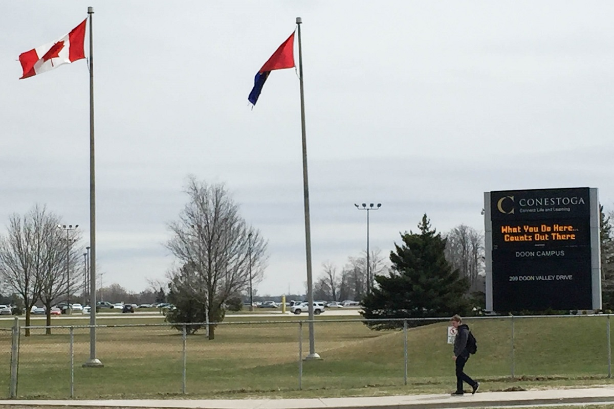 A student walks past the Conestoga College sign in Kitchener, Ont.