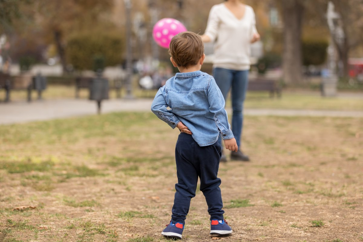 Toddler scratching back with a hand while playing in the park.