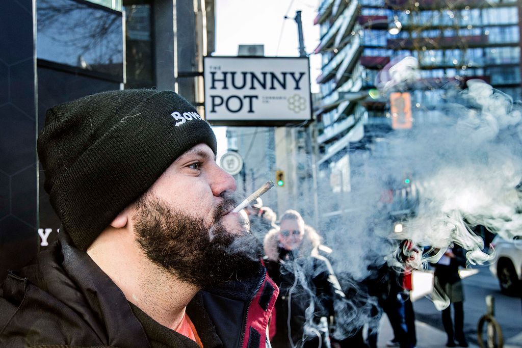 Cannabis educator Jonathan Hirsh smokes a joint he purchased outside the Hunny Pot Cannabis Co. store in Toronto.