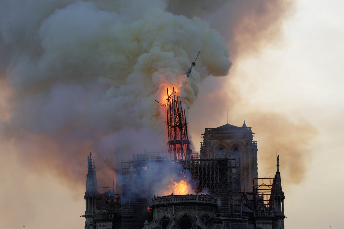 The steeple engulfed in flames collapses as the roof of the Notre-Dame de Paris Cathedral burns on April 15, 2019 in Paris. (Photo by Geoffroy VAN DER HASSELT / AFP) (Photo credit should read GEOFFROY VAN DER HASSELT/AFP/Getty Images).