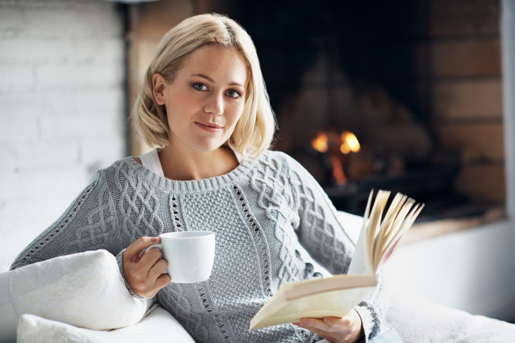 A young woman enjoying her novel with a hot drink while sitting inside near a fireplace.