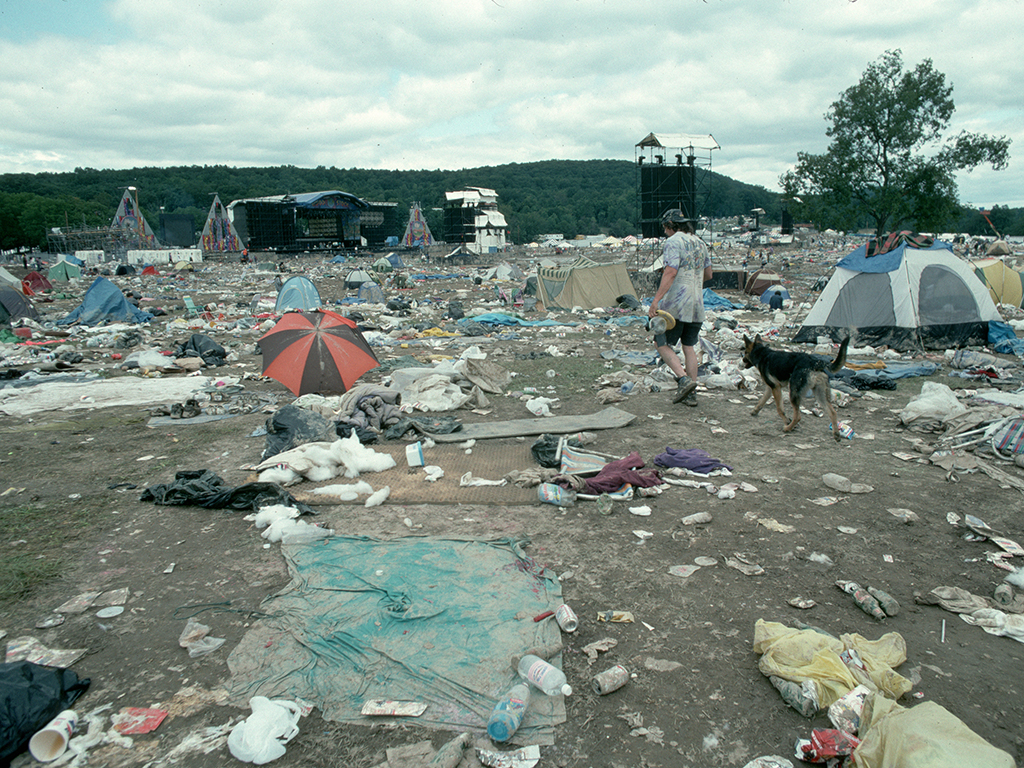 A man and his dog walk through the trash and debris left behind by festivalgoers on the concert grounds after the end of Woodstock '94, a three-day rock music festival in Saugerties, New York.