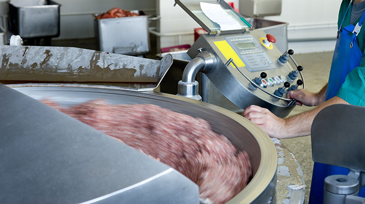 An operator controls a meat processing machine in this undated file photo.