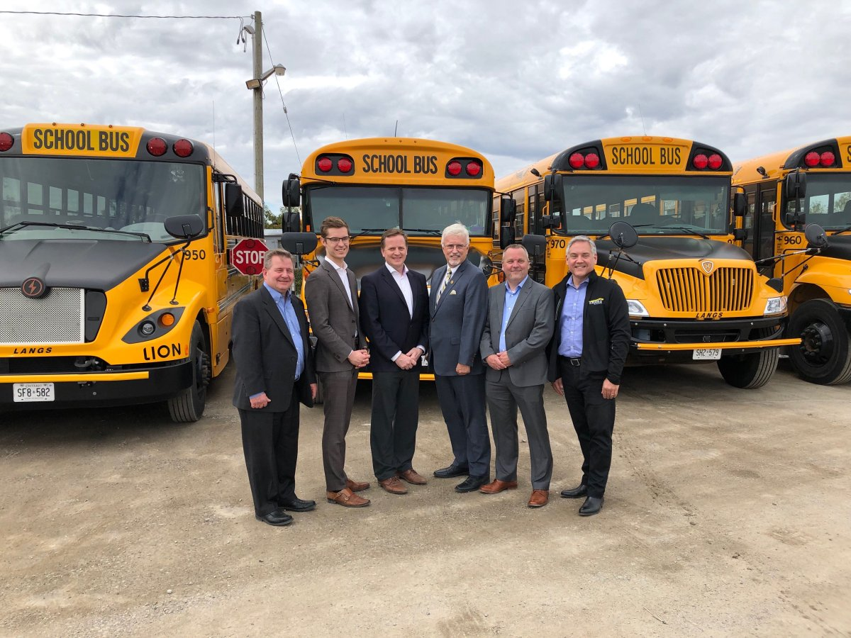 Transportation Minister Jeff Yurek (third from left) stands with fellow MPPs and a number of bus operators in the yard of Langs Bus Lines in south London, Ont.