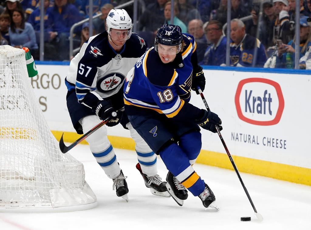 St. Louis Blues' Robert Thomas (18) handles the puck as Winnipeg Jets' Tyler Myers (57) defends during the second period in Game 3 of an NHL first-round hockey playoff series Sunday, April 14, 2019, in St. Louis. (AP Photo/Jeff Roberson).