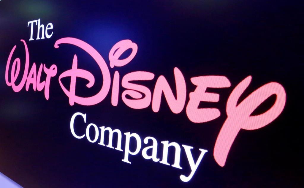 FILE - In this Aug. 7, 2017, file photo, The Walt Disney Co. logo appears on a screen above the floor of the New York Stock Exchange.