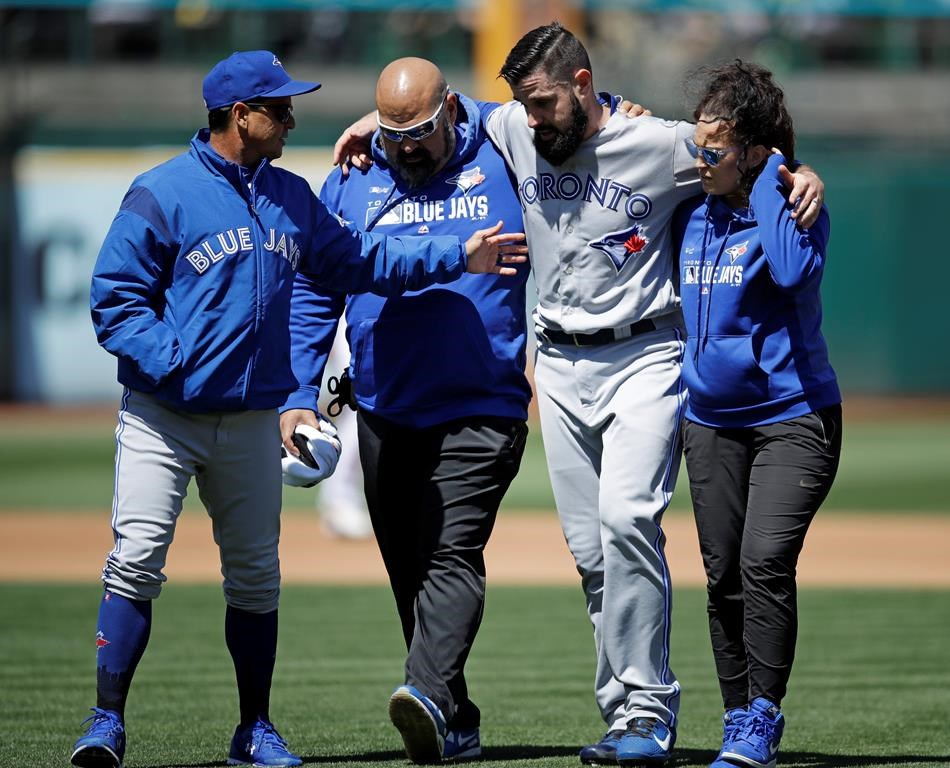 An ACL tear in the left knee forced an early end for the season of Toronto Blue Jays pitcher Matt Shoemaker, second from right, in April 2019.