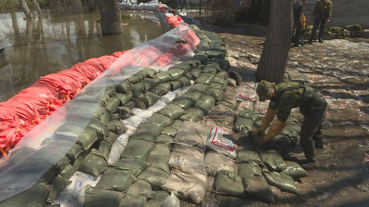 Canadian Army reservists work with municipal workers to plug a breach in a dike in Pierrefonds.