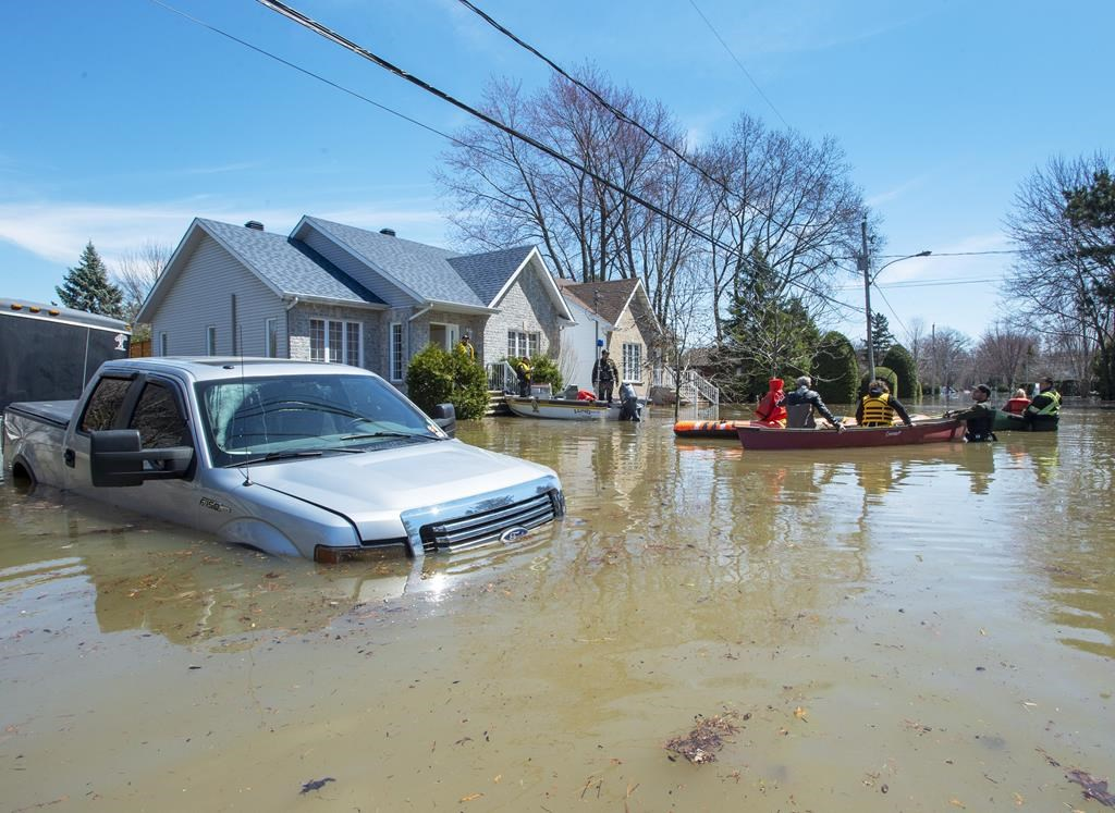 Quebec Provincial Police officers escort evacuees to retrieve belongings from their flooded homes on Monday, April 29, 2019 in Ste.Marthe-sur-la-Lac, Que.