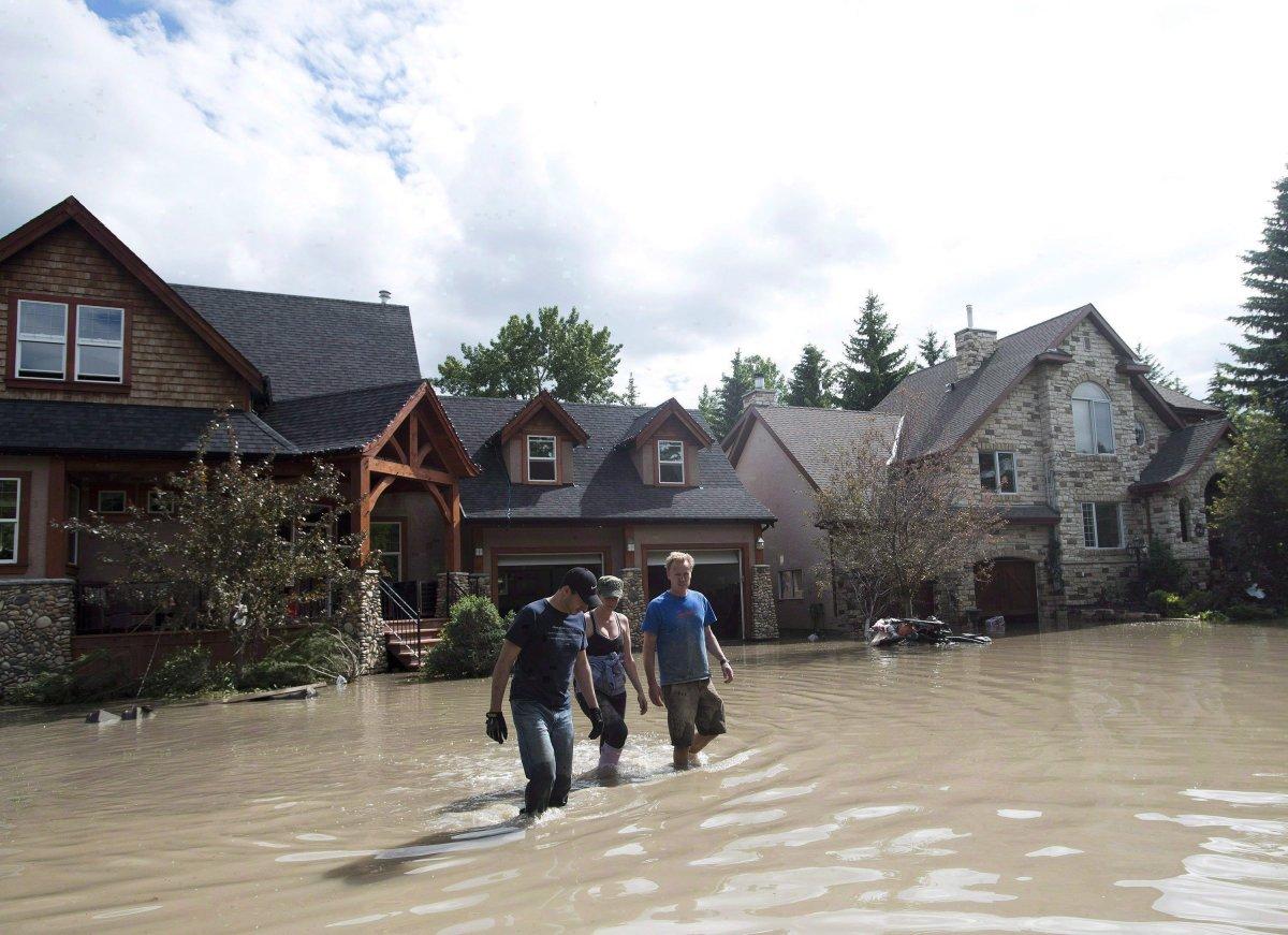 Residents walk through flood waters in Calgary on June 24, 2013.