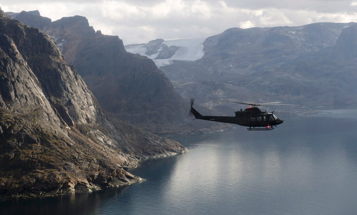 A Canadian military Griffon helicopter flies along the shoreline of Baffin Island on Tuesday August 26, 2014.