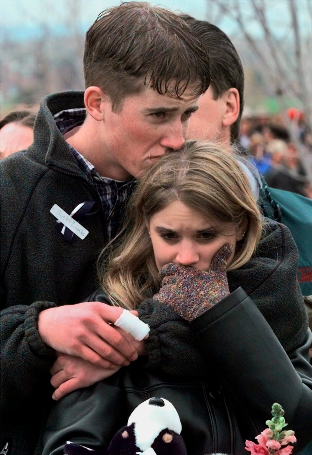 FILE - In this April 25, 1999 file photo, shooting victim Austin Eubanks hugs his girlfriend during a community wide memorial service in Littleton, Colo., for the victims of the shooting rampage at Columbine High School the previous week.