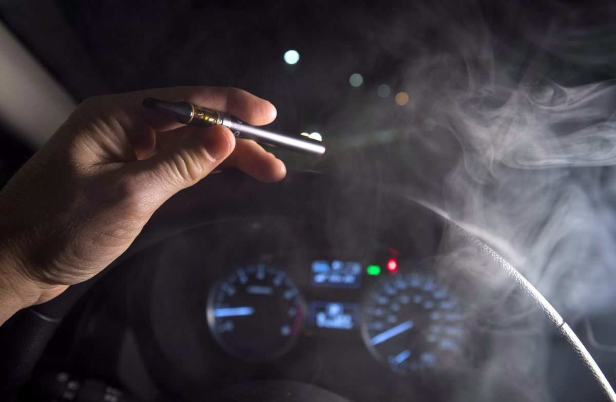 In this photo illustration, smoke from a cannabis oil vaporizer is seen as the driver is behind the wheel of a car in North Vancouver, B.C.