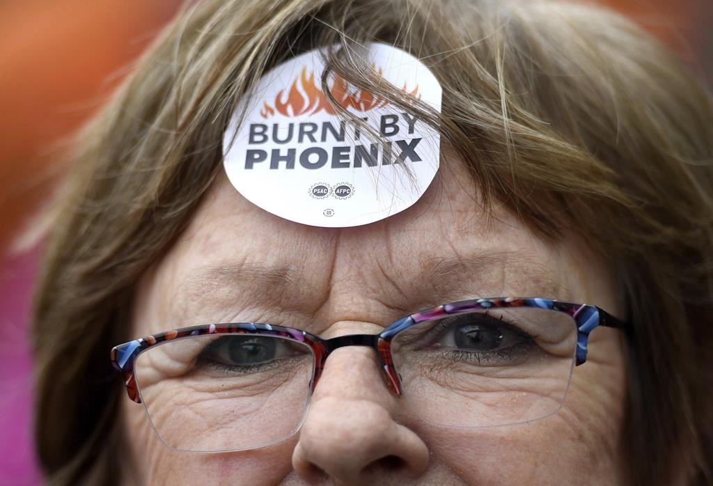 """Shirley Taylor wears a """"Burnt by Phoenix"""" sticker on her forehead during a rally against the Phoenix payroll system outside the offices of the Treasury Board of Canada in Ottawa on February 28, 2018."""
