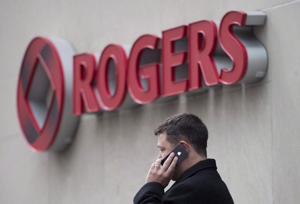 A man speaks on a mobile phone outside Rogers Communications Inc.'s annual general meeting of shareholders in Toronto on April 22, 2014. THE CANADIAN PRESS/Darren Calabrese.