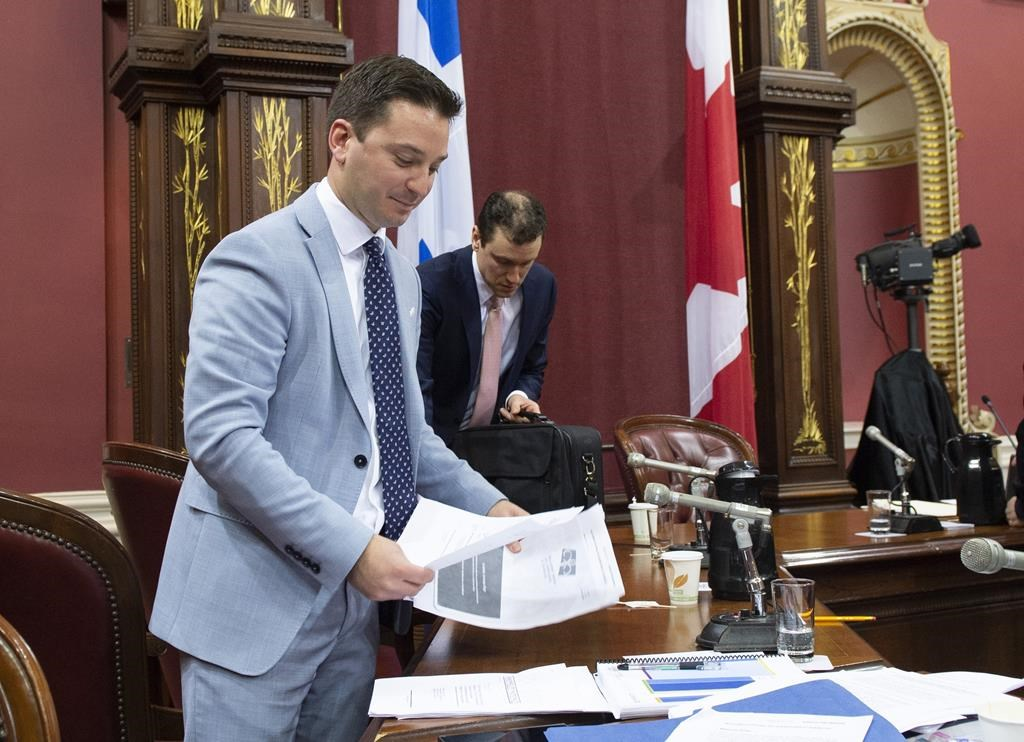 Quebec Minister of Immigration, Diversity and Inclusiveness Simon Jolin-Barrette picks up documents on the first day of a legislature committee studying a bill on secularism, Tuesday, May 7, 2019 at the legislature in Quebec City. Hearings into Quebec's secularism bill veered off track Thursday when a former senator drew a connection between the Muslim head scarf, female genital mutilation and forced marriage.